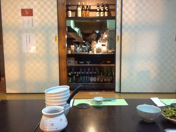 小上がりの部屋からカウンター越しに調理場が見える。