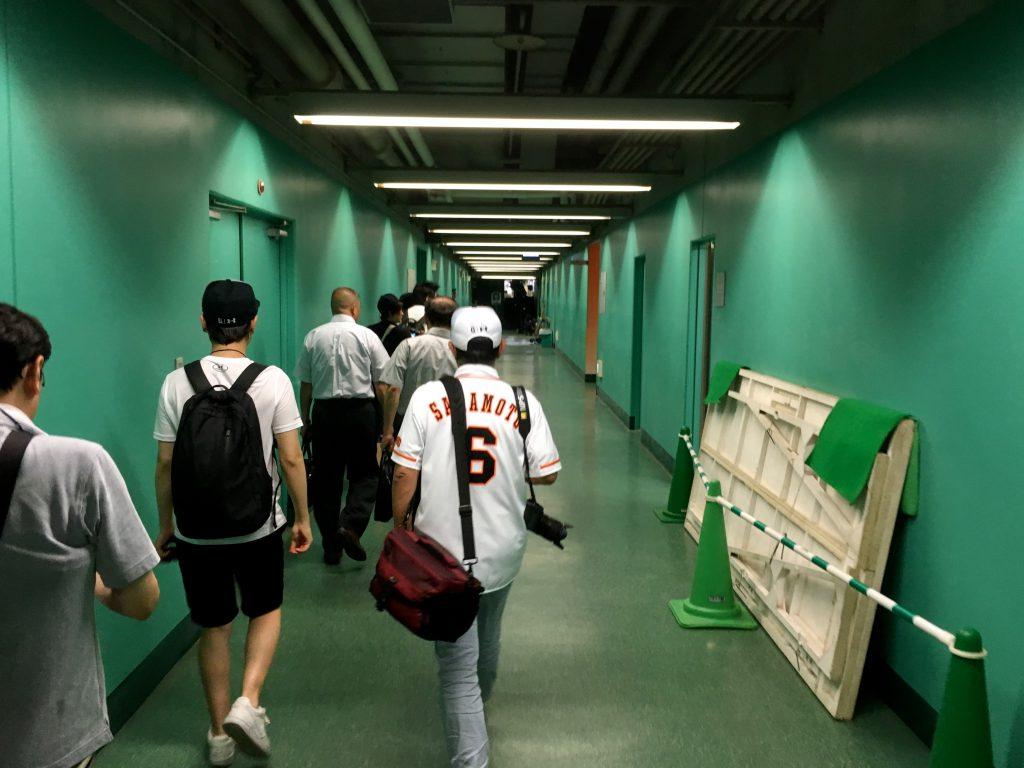 グリーンの壁の長い廊下を歩いて進む
