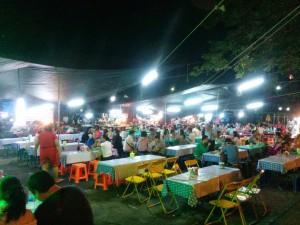 屋台村で大勢の人が料理を楽しむ