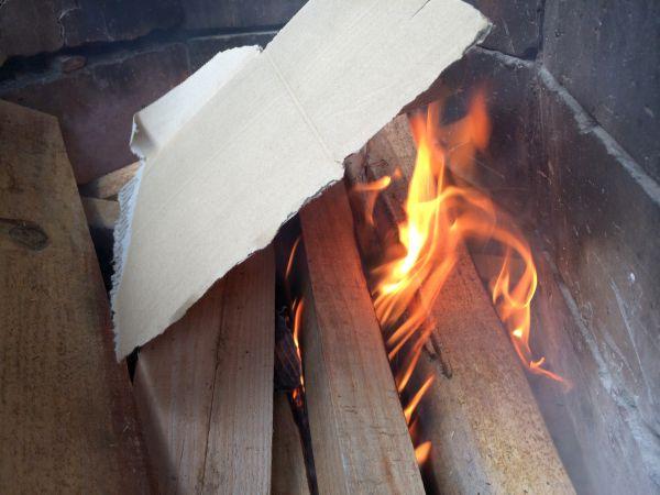 薪に火が回りやすいように組んで、新聞紙とダンボールに着火。