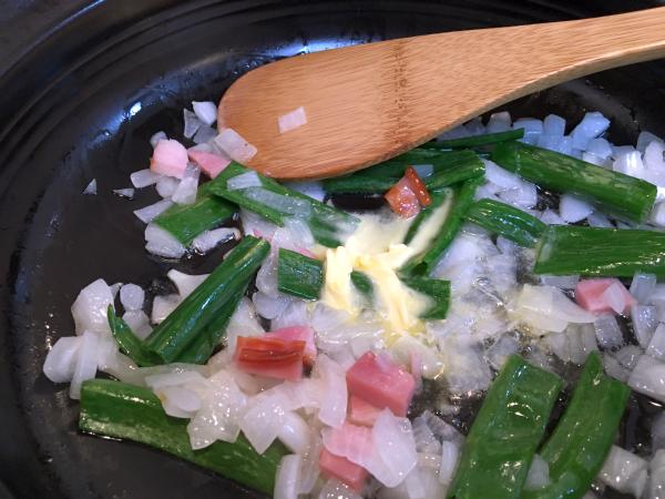 タマネギに続いて、タマネギの青葉、ベーコン、そしてバターを入れてさらに炒めます。
